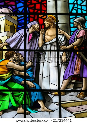 GUIMARAES, PORTUGAL - AUGUST 7, 2014: Stained glass window depicting Jesus accused before Pontius Pilate in the Santos Passos church in Guimaraes, Portugal. - stock photo