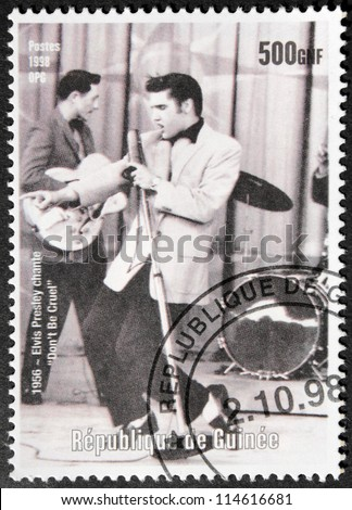 GUINEA - CIRCA 1998. A postage stamp printed by GUINEA shows image portrait of famous American singer Elvis Presley (1935-1977), circa 1998. - stock photo