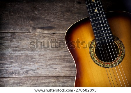 Guitar against a rustic wood background - stock photo