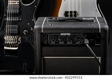 Guitar amp in focus of the camera. In the background there are some parts of electric and bass guitars of different colors. - stock photo