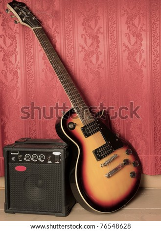 Guitar and amp, red background - stock photo