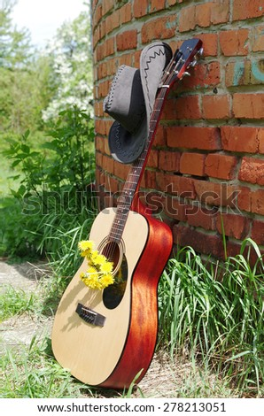 Guitar and cowboy hat near the brick wall