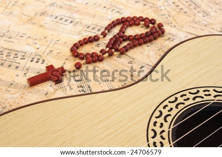 Guitar and  crucifix on a music sheet - stock photo
