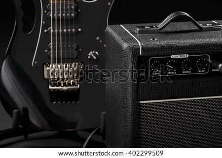 Guitar and its amp in foreground. Nice classical black color of musical instrument and equipment.  - stock photo
