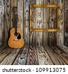 Guitar and picture frame in vintage wood room. - stock photo