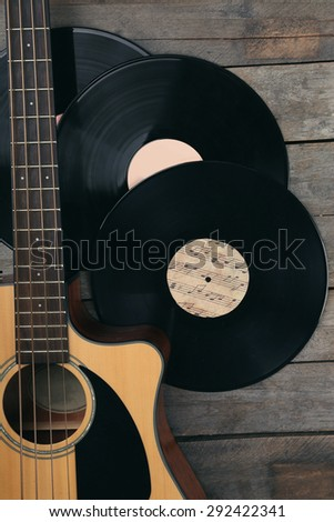 Guitar and vinyl records on wooden table close up - stock photo