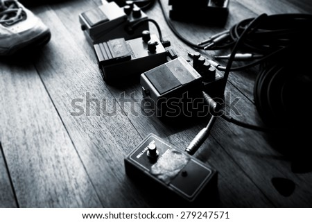 Guitar audio processing effects on the floor. Electric guitar stomp box effectors and cables on studio floor.  Intentionally shot with low key shadows. - stock photo