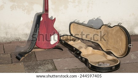 guitar case with coins and bills - stock photo