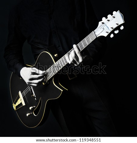 Guitar electric Guitarist playing black music instrument in hands closeup on black - stock photo