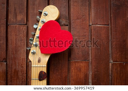 Guitar head stock with red heart on wooden background - stock photo
