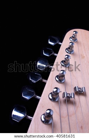 Guitar headstock, strings and tuners against a black background - stock photo
