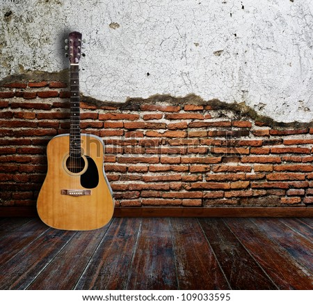 Guitar in grunge room. - stock photo