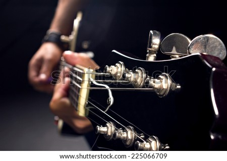 guitar in man's hands, close-up shot, dark background - stock photo