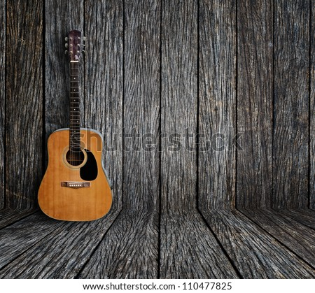 Guitar in vintage wood room. - stock photo