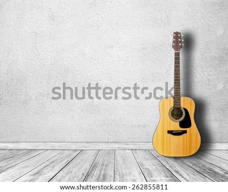 Guitar in white room. - stock photo