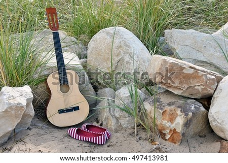 guitar leaning on rocks in beach sand with red and white striped shoes
