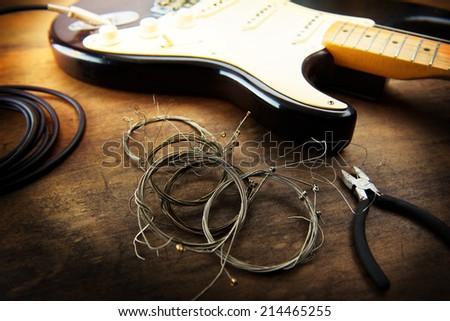 Guitar maintenance. Rolled old guitar strings and an electric guitar. Changing guitar strings. - stock photo