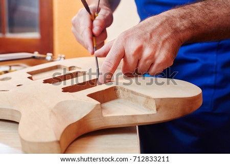 Guitar maker works on handmade guitar at carpenter's workshop