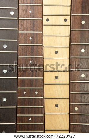 Guitar necks aligned, Rosewood, maple and ebony fingerboard necks - stock photo
