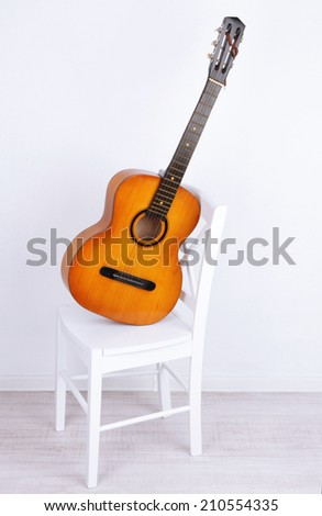 Guitar on a white wooden chair on the floor on white background