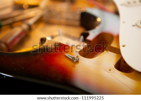Guitar on guitar repair desk. Electric guitar on a guitar repair work shop. Neck and pickguard detached. Double cutaway solid body guitar, sunburst color. Shallow depth of field. - stock photo