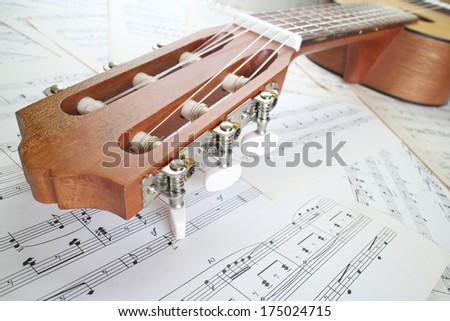 guitar on music sheet , headstock closeup - stock photo