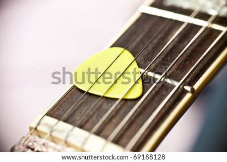 Guitar pick between strings of a fretboard - stock photo
