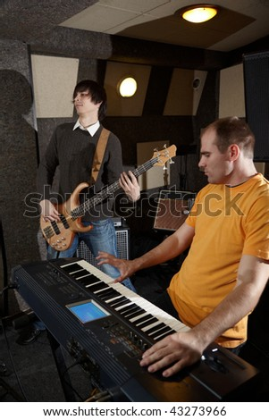 guitar player and keyboard player is working in studio. focus on distant part of synthesizer - stock photo