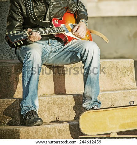 guitar player in the street with an open guitar case in vintage tone - stock photo