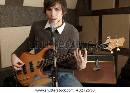 guitar player is playing and singing in studio. focus on guitar head - stock photo