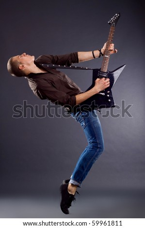 Guitar player isolated against dark back ground - stock photo