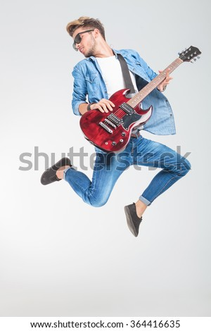 guitar player jumping and looking back in studio while playing rock and roll - stock photo