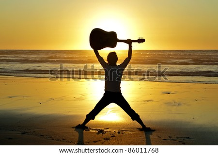 Guitar player on the beach at sunset