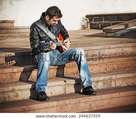 guitar player on the stairs in vintage tone effect - stock photo