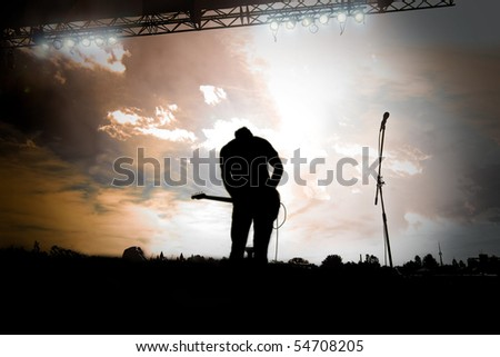 Guitar player playing a outdoor concert at sunset - stock photo