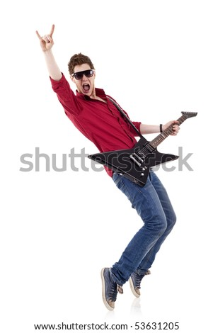 Guitar player playing his guitar on his tip toes and make a rock and roll sign
