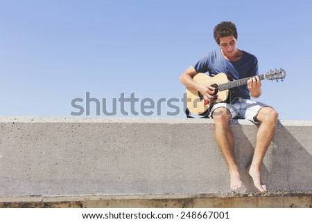Guitar player practicing on the pier - stock photo