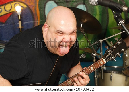 Guitar player with attitude sticking his tongue out while playing.