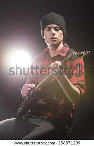 Guitar player. Young man is playing guitar against in dark room with lights behind him. - stock photo