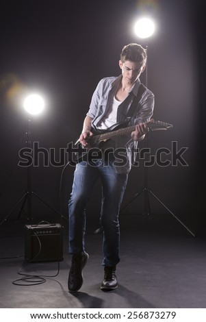 Guitar player. Young man is playing guitar against in dark room with lights behind him.