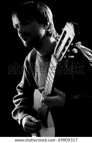 Guitar playing. Guitarist. Young man playing acoustic six-string guitar. Guitarist professional isolated on black background. Black and white photo - stock photo
