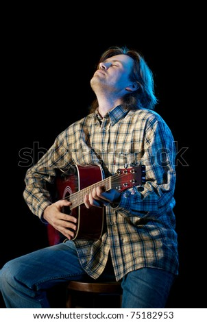 Guitar playing. Man with long hair playing acoustic six-string guitar. Isolated on black background. - stock photo