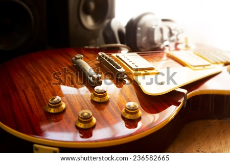 Guitar recording scene. An electric guitar, and a professional grade headphones, and a monitor speaker in the background.  - stock photo
