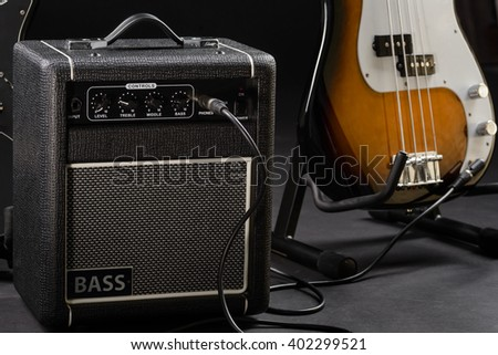 Guitar with bass amp before giving a concert. Musical intruments are ready to make a lot of people happy. Brown with white bass guitar. - stock photo