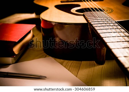 Guitar with Red Book and pen on a wooden table, Vintage style. - stock photo