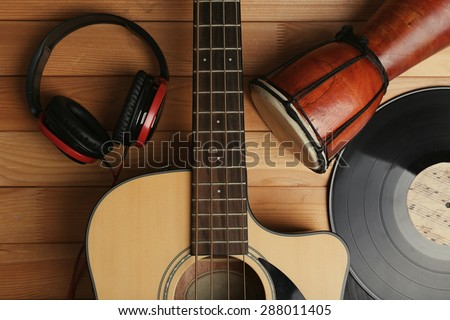 Guitar with vinyl records and African drum on wooden table close up - stock photo