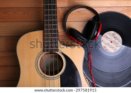 Guitar with vinyl records and headphones on wooden table close up - stock photo