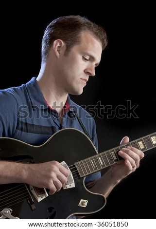Guitarist against a black background