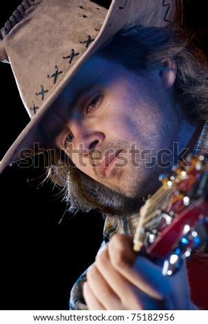 Guitarist. Closeup shoot of man wearing cowboy hat playing on a acoustic guitar. Isolated on black background. - stock photo