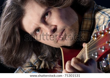 Guitarist. Closeup shoot of man with long hair plaing on a acoustic guitar. - stock photo